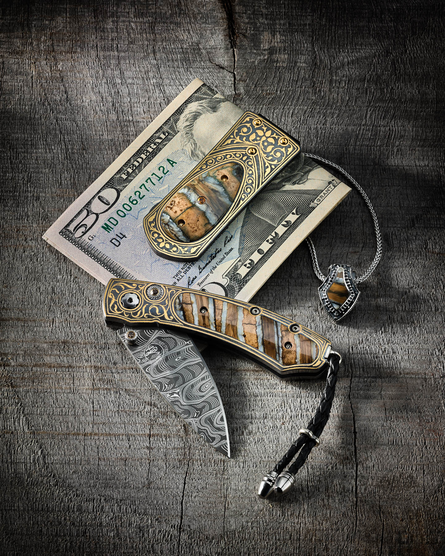 William Henry money clip, knife, and necklace on aged walnut by Steve Temple Photography