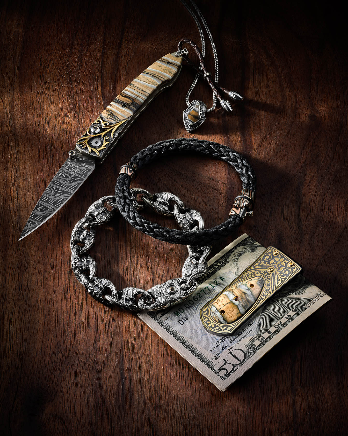 William Henry money clip, knife, and necklace on walnut by Steve Temple Photography